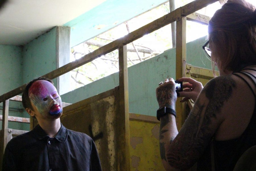 Instructor Megan St. Clair films Anna Blankenship as she acts out a creepy scene in an abandoned bathroom for St. Clair's art piece. When filming the video, both St. Clair and Blankenship along with Hugo Zelada-Romero would use strobe lights, different masks and other props to create a creepy atmosphere.