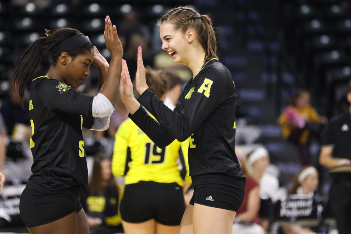 Junior Tabitha Brown (left) high fives senior Mikaela Raudsepp (right) during the Shockers victory over UCF. (Oct. 1, 2017)