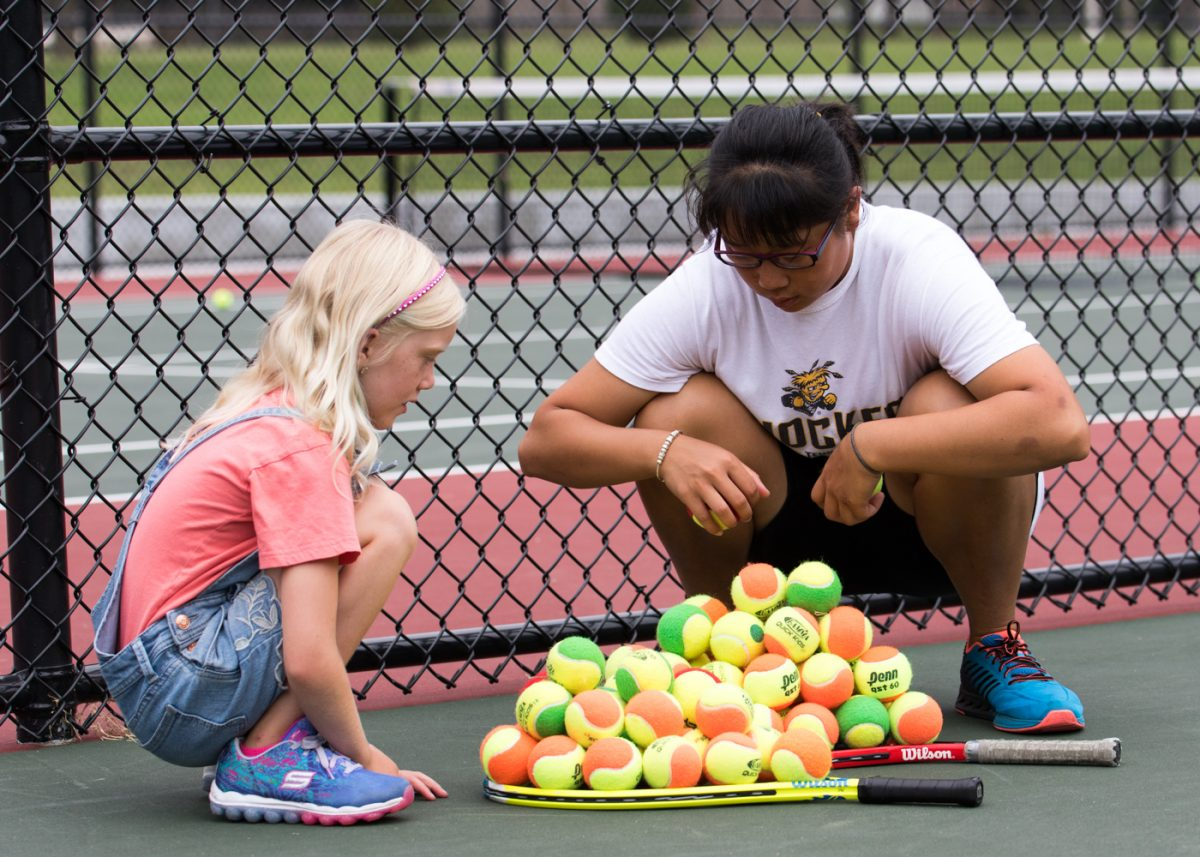 Ting-Ya Hsu picks up balls and talks with a youth during the free clinic held at the new courts in Fairmount Park in August
