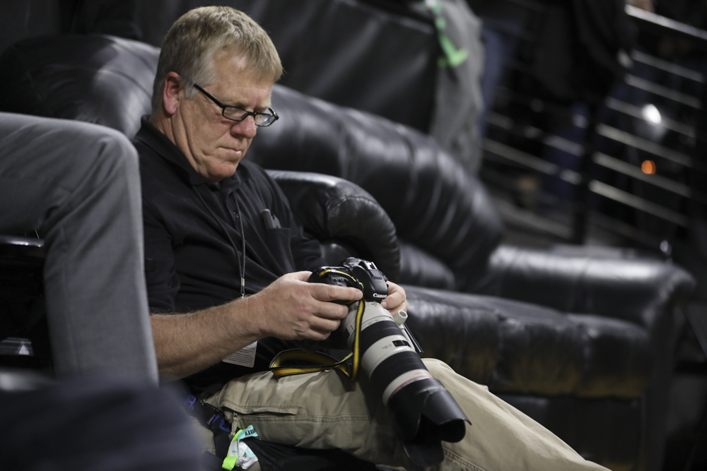 Jeff Tuttle looks at photos on the back of his camera during the Shockers vs. Newman.