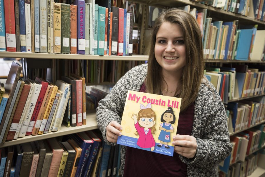 Amy Lightfoot, junior Communication Sciences and Disorders student, poses with a copy of her book, My Cousin Lili in Ablah Library. Lightfoots inspiration for the book was her cousin who has autism.