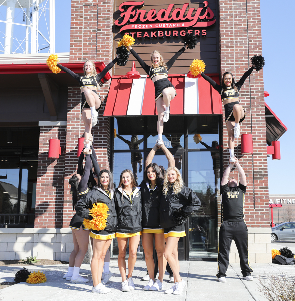 The Wichita State cheerleading team stunts outside of a Freddy's Frozen Custard & Steakburgers.