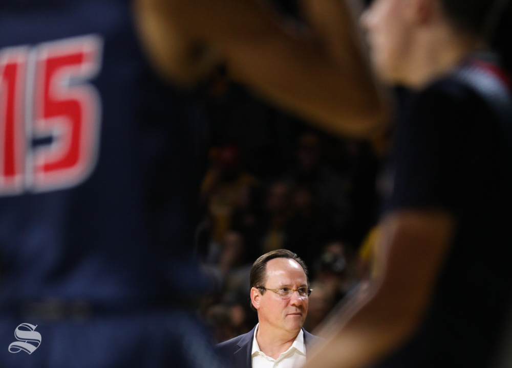 Two Newman players frame Wichita State Shockers head coach Gregg Marshall during the charity exhibition game in Koch Arena.