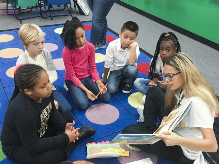 Gabriela Reyna, WSU athlete, reads a book to Heather Crumps third grade class at Adams Elementary.