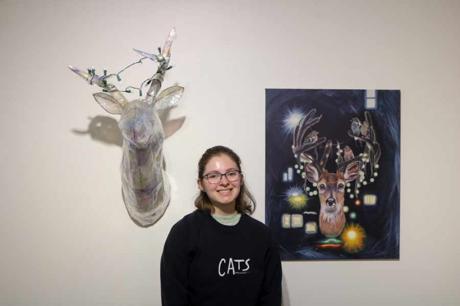 Theresa Wolf poses in front of her work, New Catch and Urban Outgrowth, in the Cadman Art Gallery.
