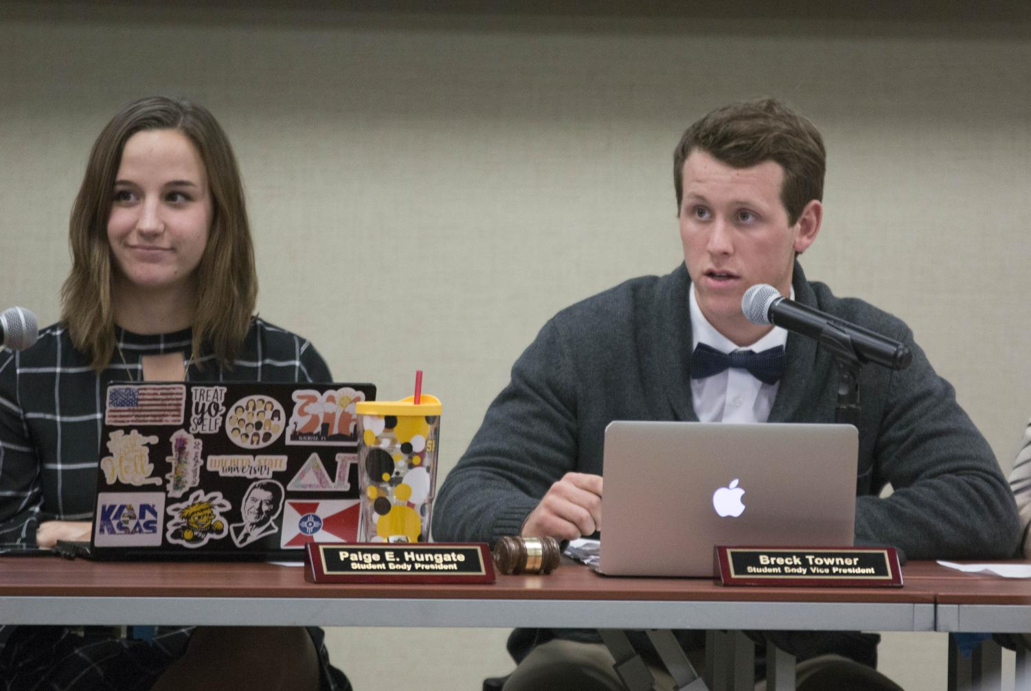 Breck Towner, student body vice president, speaks to a senator during the meeting Wednesday evening.