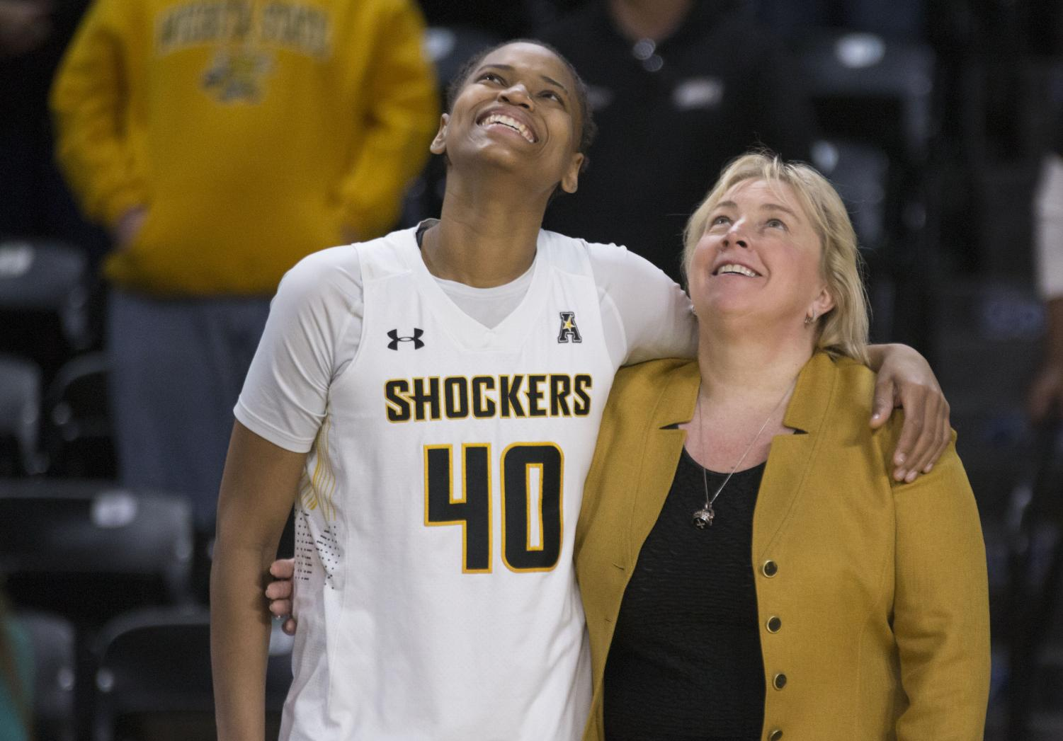 February 24, 2018: Wichita State senior Angiee Tompkins watches the senior highlight reel with head coach Keitha Adams.