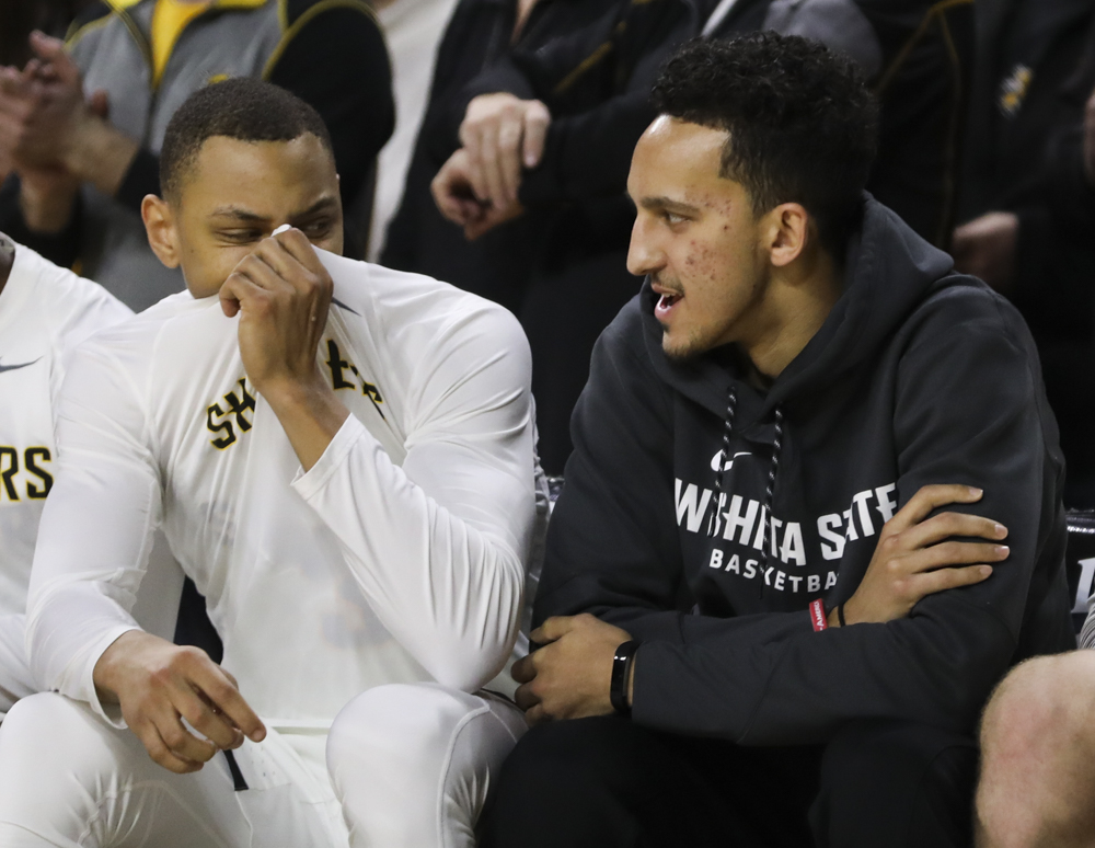 Wichita State guard C.J. Keyser covers his mouth as Wichita State guard Landry Shamet talks before tipoff against the Tulane Green Wave at Koch Arena. Shamet did not suit up.