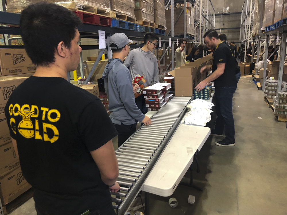 Cortez Schenck and teammates package food boxes at the Kansas Food Bank. The boxes include shelf-stable healthy food options.