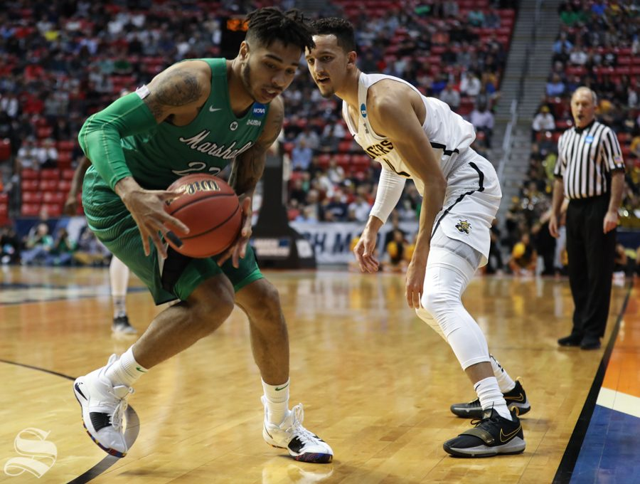 Wichita State guard Landry Shamet (11) guards Marshall guard Rondale Watson (23) during the First Round game of the NCAA men's college basketball tournament in San Diego.