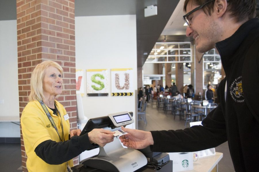 Cashier Maureen Coleman swipes a students meal card in the Shocker Dining Hall.