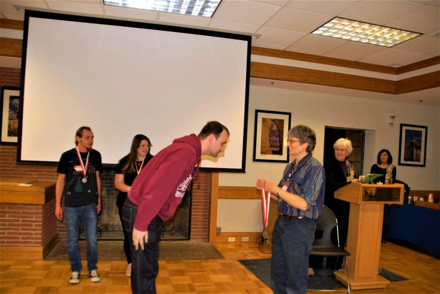 Russell Greenall-Sharp bows and accepts his medal for first place in the tanka poem contest. Participant submitted poems in two divisions: English and Japanese. Greenall-Sharps tanka was written entirely in Japanese.