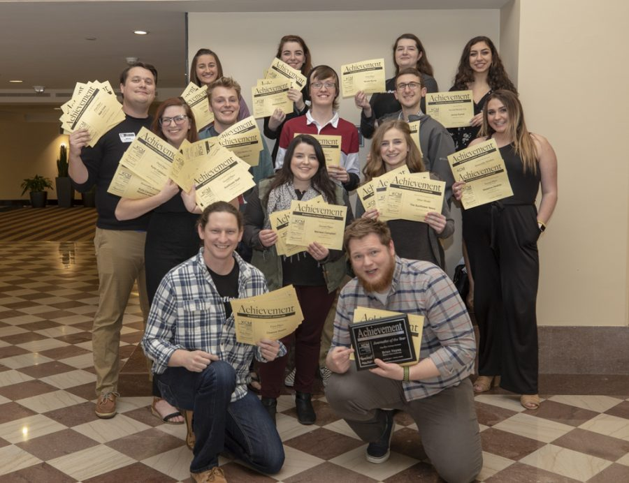 The Sunflower staff poses with the 52 awards, including 3 Journalist of the Year awards,  they won at the Kansas Collegiate Media awards.