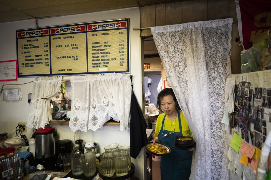 Manna Wok owner Kye Chon brings a dish to customers in the dining room of the restaurant.