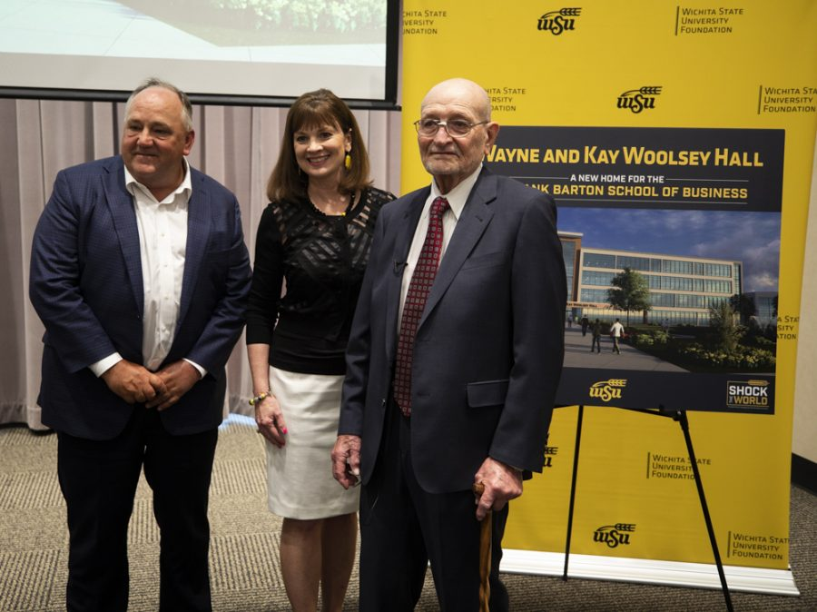 Steve Feilmeier, executive vice president of CFO of Koch Industries, President and CEO of the WSU Foundation Elizabeth King and Wayne Woolsey pose for photos with the rendering of new hall.