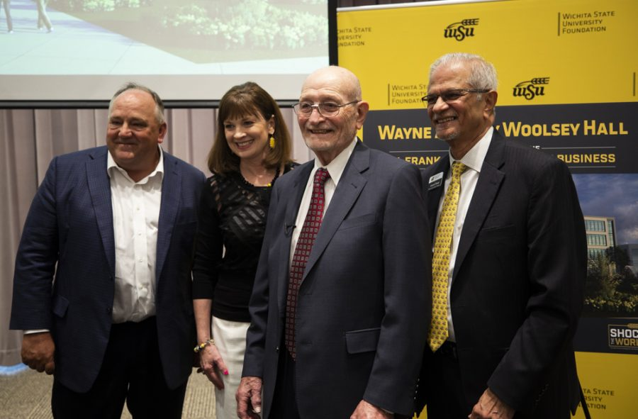 Steve Feilmeier, executive vice president of CFO of Koch Industries, President and CEO of the WSU Foundation Elizabeth King, Wayne Woolsey and Dean of the School of Business Anand Desai pose for photos with the rendering of new hall.