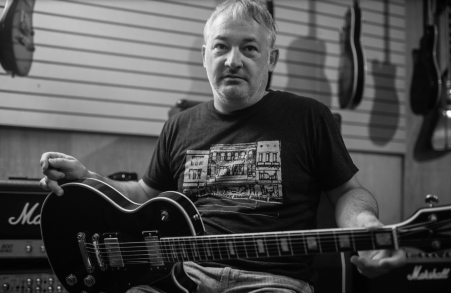 Former Wichita State English instructor Michael Cissell sits with his guitar inside Phil Uhlik Music while discussing the release of his poetry book, Cutting Songs of the Butcher Son. Five days after the interview, Cissell passed away.
