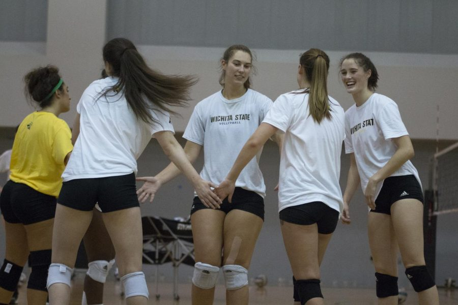 Wichita State volleyball players celebrate after completing a successful play during practice in Koch Arena.