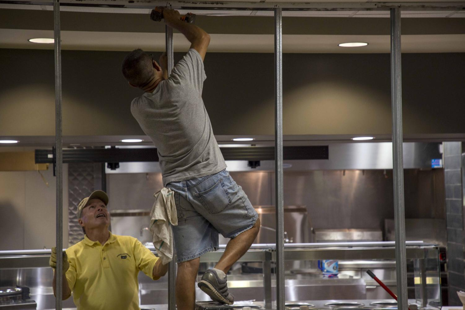 Construction crew members install paneling for Panda Express. Panda Express will open early next week in the Rhatigan Student Center.