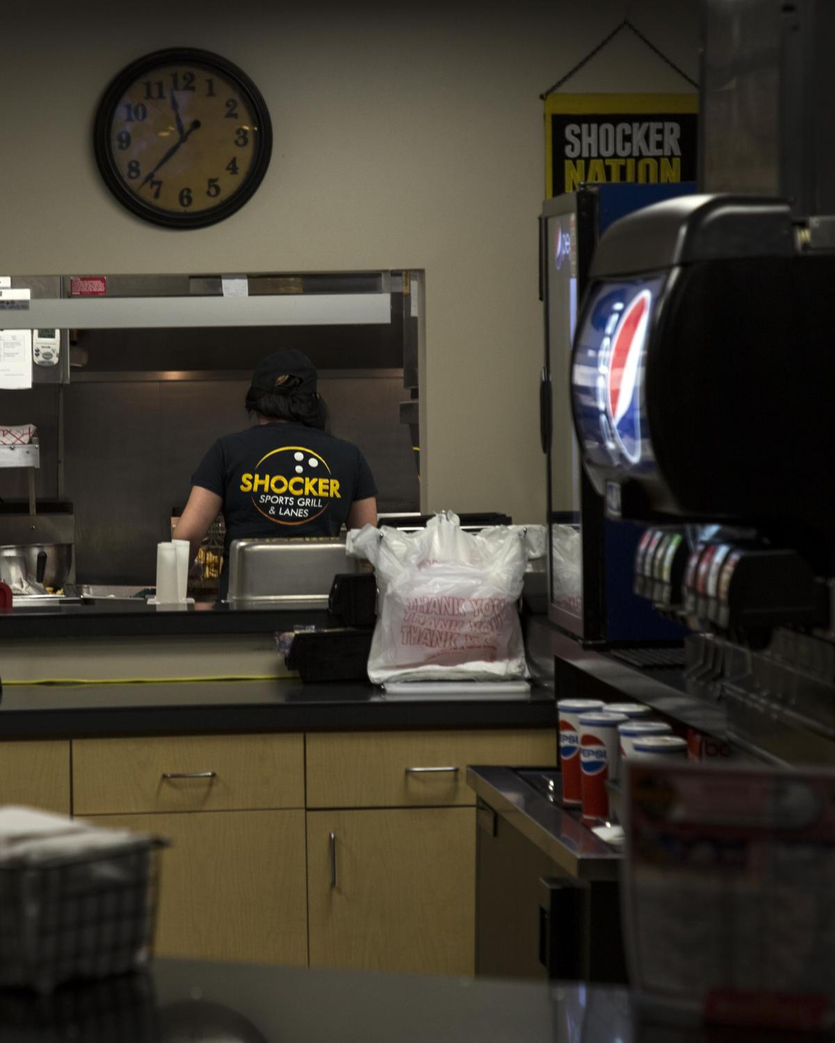 An employee prepares food for Shocker Sports Grill and Lanes customers. Shocker Sports Grill and Lanes is located in the basement of the Rhatigan Student Center.
