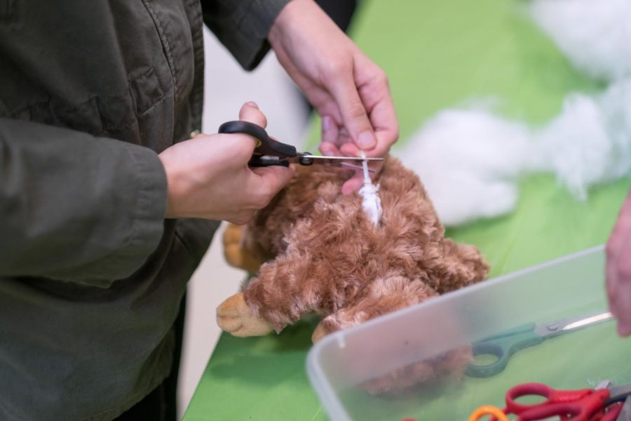 The doll is being stitched after it has been fully stuffed.