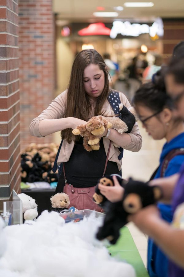 A junior majoring in Business, Jacky Enriquez, builds a stuffed monkey to support the youth living with cancer.