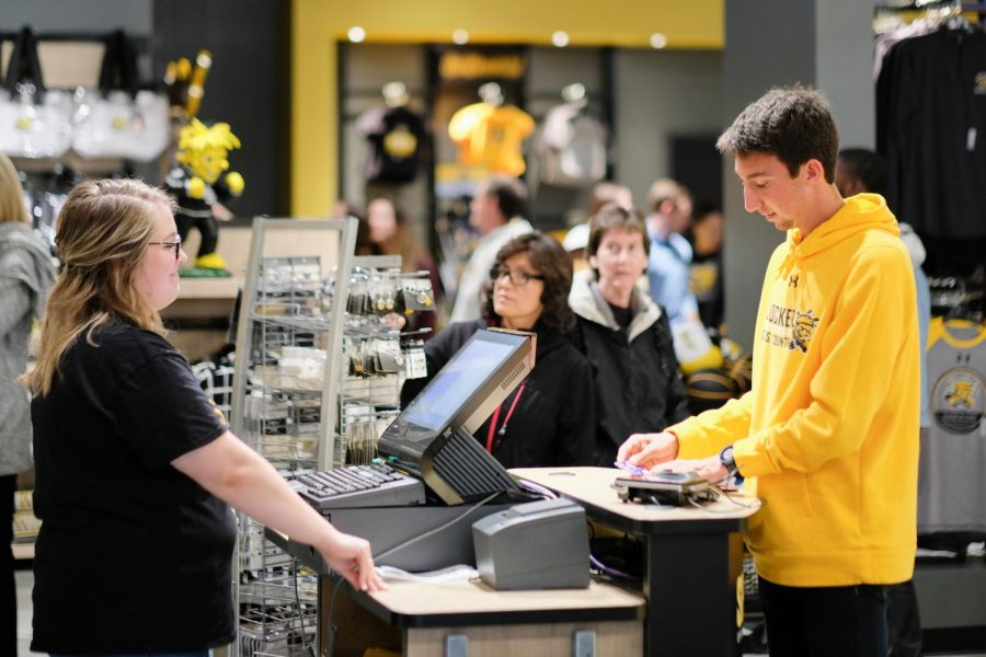 Joshua Klein, a junior majoring Accounting, makes a purchase at the Shocker Store on the grand opening day.
