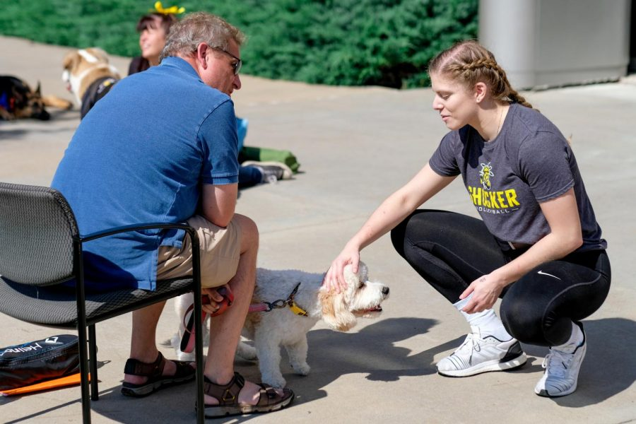 Alayna Maslinski, a sophomore majoring in Exercise Science and Biology, plays with Mitty, a Cavachon dog, at Love On A Leash outside of Study Hall, on Friday, Oct. 5, 2018.