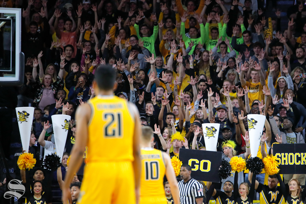 Wichita State's student section raises their hands during the basketball game on Oct. 30, 2018 in Koch Arena.