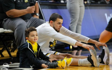 November 7, 2018: Adriel, 4, stretches with his dad before the game on Nov. 6, 2018. Adriel is the son of Wichita State guard Ricky Torres.