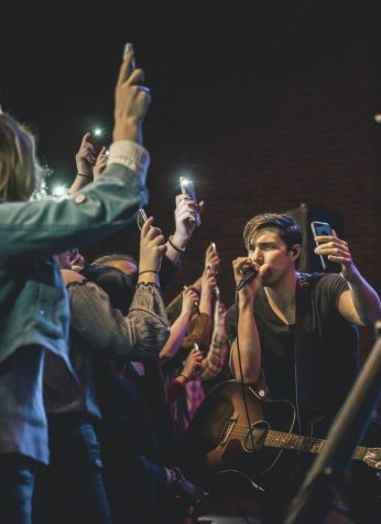FILE PHOTO: Country music singer and song writer, John King, records a video for his Instagram story during his performance.