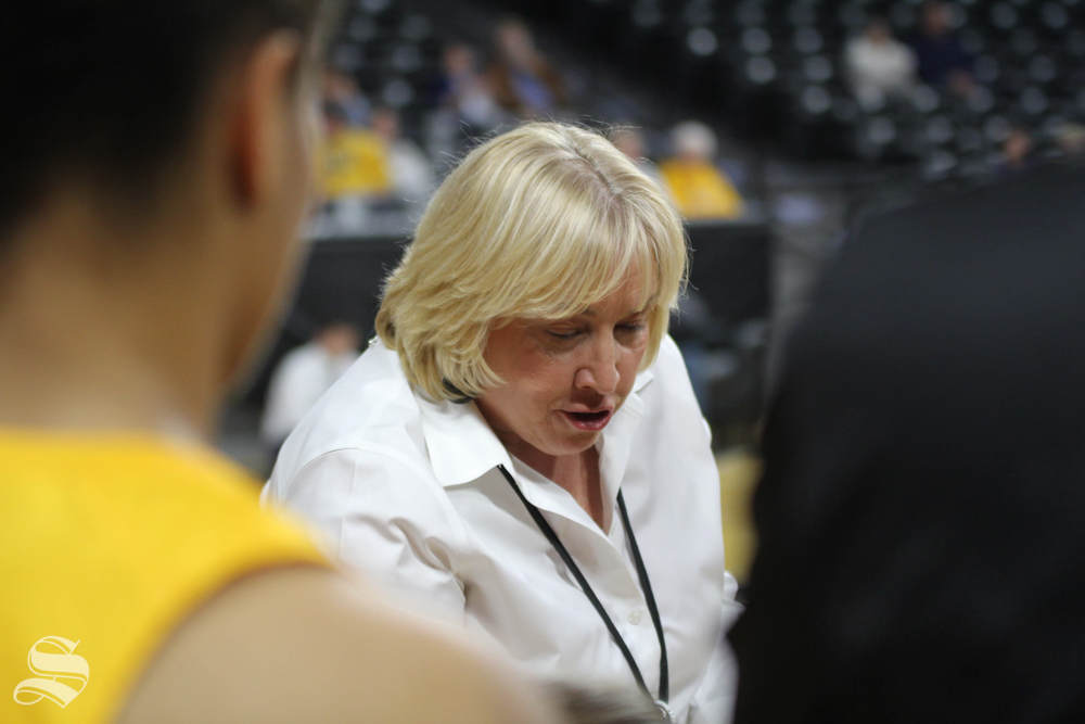 Women's basketball coach Keitha Adams instructs players at the beginning of halftime.