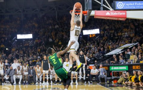Wichita State freshman Erik Stevenson makes a dunk over Baylor guard Devonte Bandoo on Dec. 1, 2018 in Koch Arena.