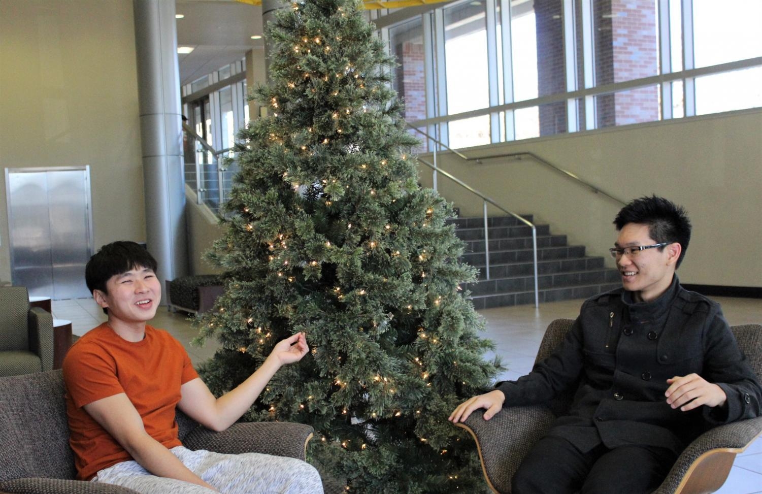 Malaysian international students Jerome Jun Chang Teoh (left) and Christopher Mong En Leong (right) sit in the Rhatigan Student Center. Both are staying on campus over the holidays.