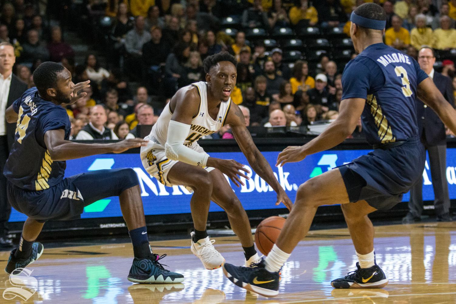Wichita State senior Samajae Haynes-Jones attempts to drive past Oral Roberts defenders during the game at Koch Arena Wednesday, Dec. 19, 2018.