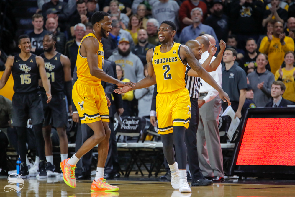 Wichita State freshman Jamarius Burton cheers with senior Markis McDuffie after drawing a foul towards the end of the first half. WSU played UCF on Jan. 16, 2019 at Charles Koch Arena.