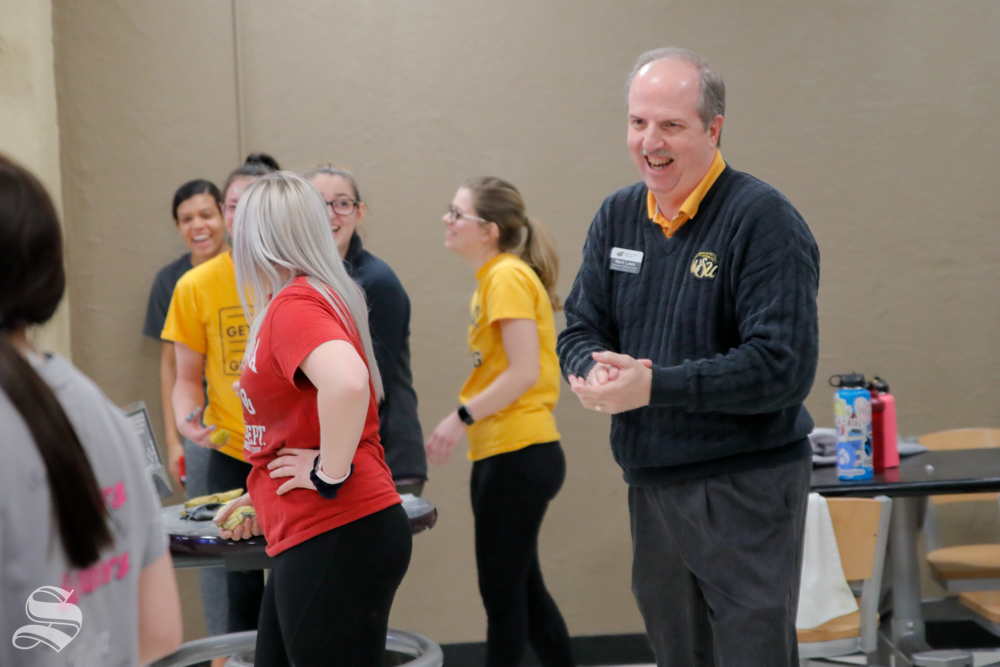 Mark Lewis laughs with a players of the women's bowling team on Feb. 12, 2019 at the Rhatigan Student Center.