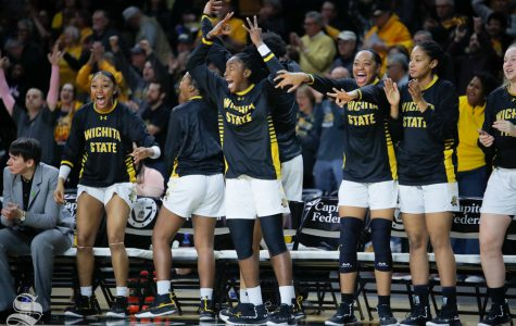 The Wichita State bench celebrates after Sabrina Lozada-Cabbage sinks the first three-point basket during the game against UConn on Feb. 26, 2019 at Charles Koch Arena. (Photo by Joseph Barringhaus/The Sunflower.)
