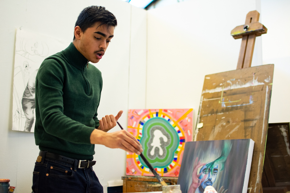 Emiliano Molina responds to questions during an interview with The Sunflower while he begins the process of painting two new pieces.