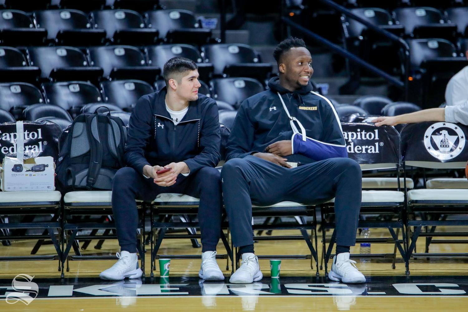 Freshman Morris Udeze sits with walk-on Tate Busse during warmups on Feb. 9, 2019.