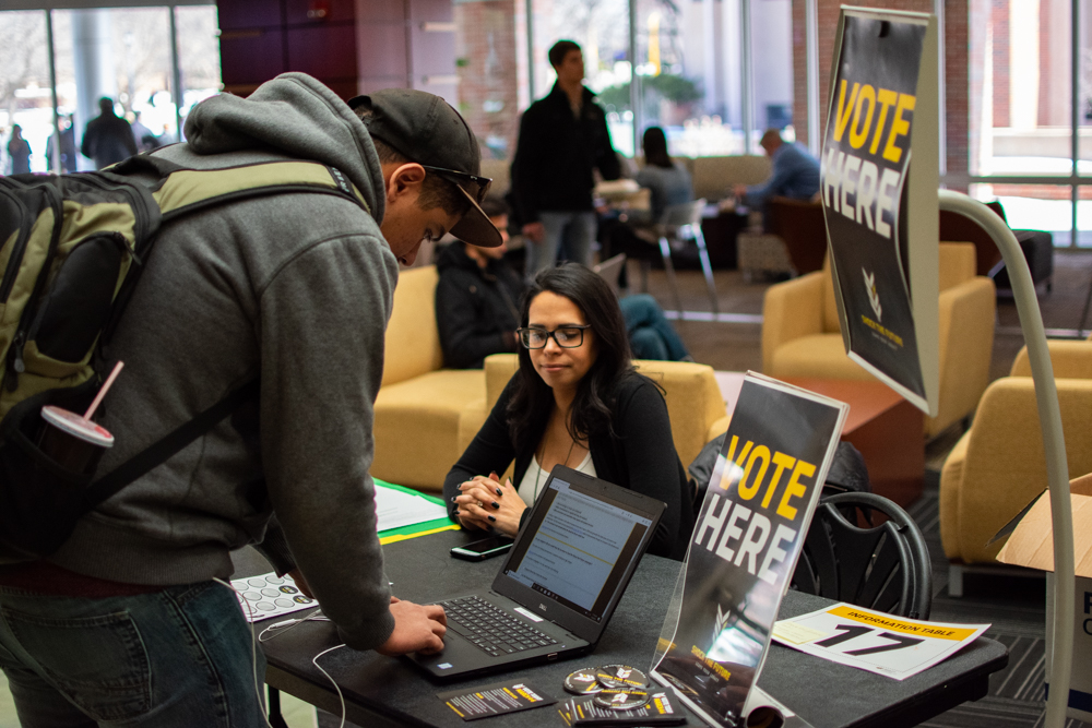 Jenny Beyer from Housing and Residence Life assists junior criminal justice major Ralph Young with voting in the Shock the Future student fee referendum Tuesday in the Rhatigan Student Center.