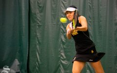 Wichita State sophomore Lingwei Kong swings for the ball during their set against Oklahoma State's Lisa Marie Rioux at the Wichita Country Club tennis complex on Sunday, March 10. (Photo by Easton Thompson/The Sunflower)