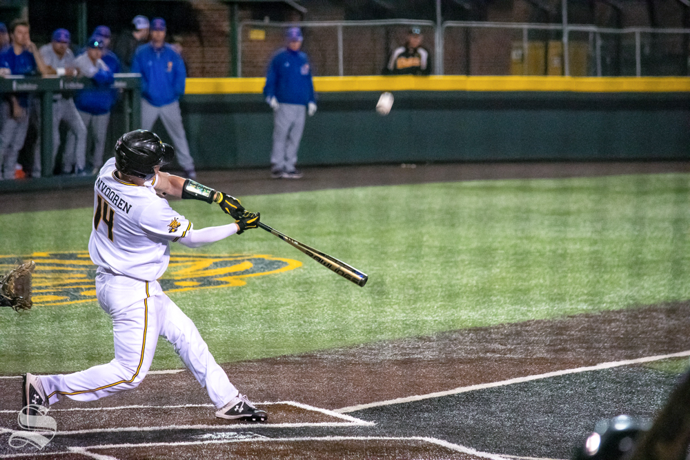 Wichita State's David Vanvooren hits a fly ball that is caught by one of Kansas University's outfielders during their game on Wednesday, March 20. (Photo by Easton Thompson/The Sunflower).