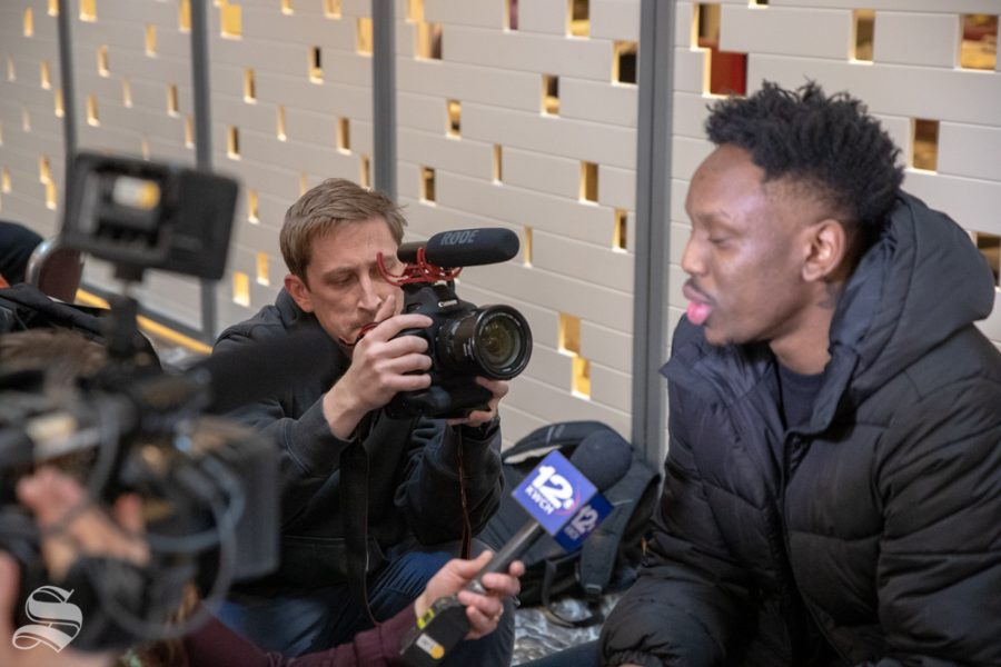 Wichita State videographer Marcus Wright follows closesly as senior Samajae Haynes-Jones is interviewed by a member of the media in the New York Marriott Marquis on April 1, 2019. (Photo by Joseph Barringhaus/The Sunflower).