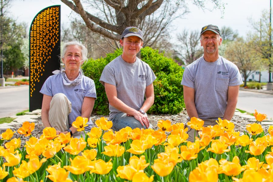 Kari Ossman, Tiffany Jehle, and Lowell Kaughman are WSU's floral department crew. Here they stand behind a tulip bed outside Ahlberg Hall.