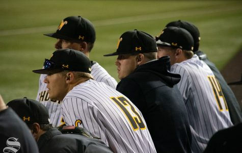 Wichita State players watch and wait for the decision to postpone the game in the seventh inning of their game against University of Central Florida on Friday, April 19. (Photos by Easton Thompson / The Sunflower).