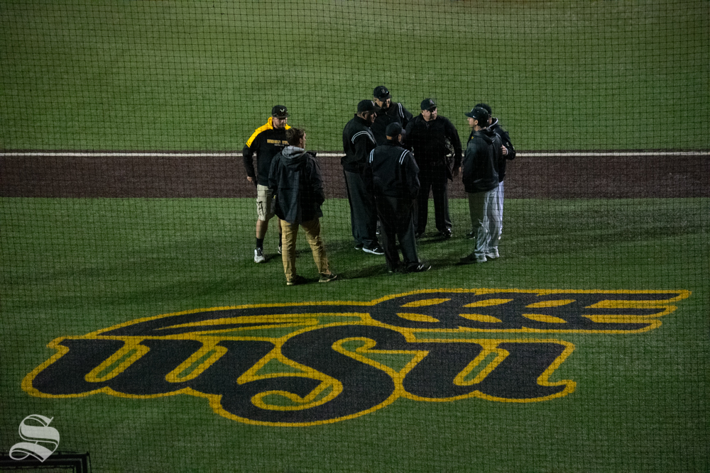 Umpires discuss with team coaches during the game on Friday, April 19. The game between Wichita State and University of Central Florida was postponed during the seventh inning until the following day due to a set of lights going out which dimmed the field. (Photos by Easton Thompson / The Sunflower).