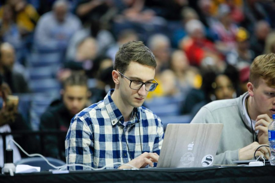 Evan Pflugradt types on a computer during a men's basketball game. (Photo by Joseph Barringhaus/The Sunflower).