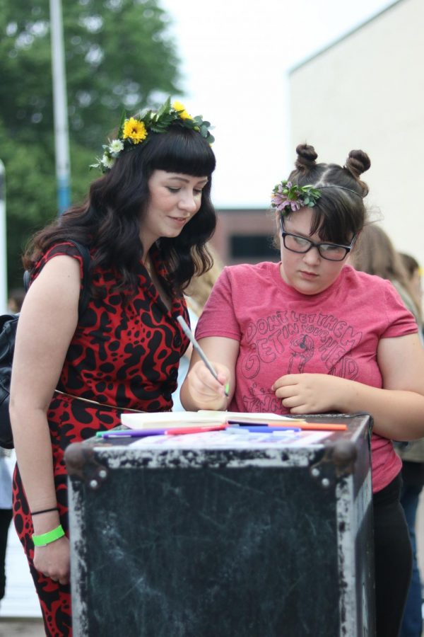Supporters wearing flower crowns donated by Beards Floral Design leave a note in the Jenny Woods guestbook at Jenny Woodstock on Saturday, May 25 at The Back Beat.