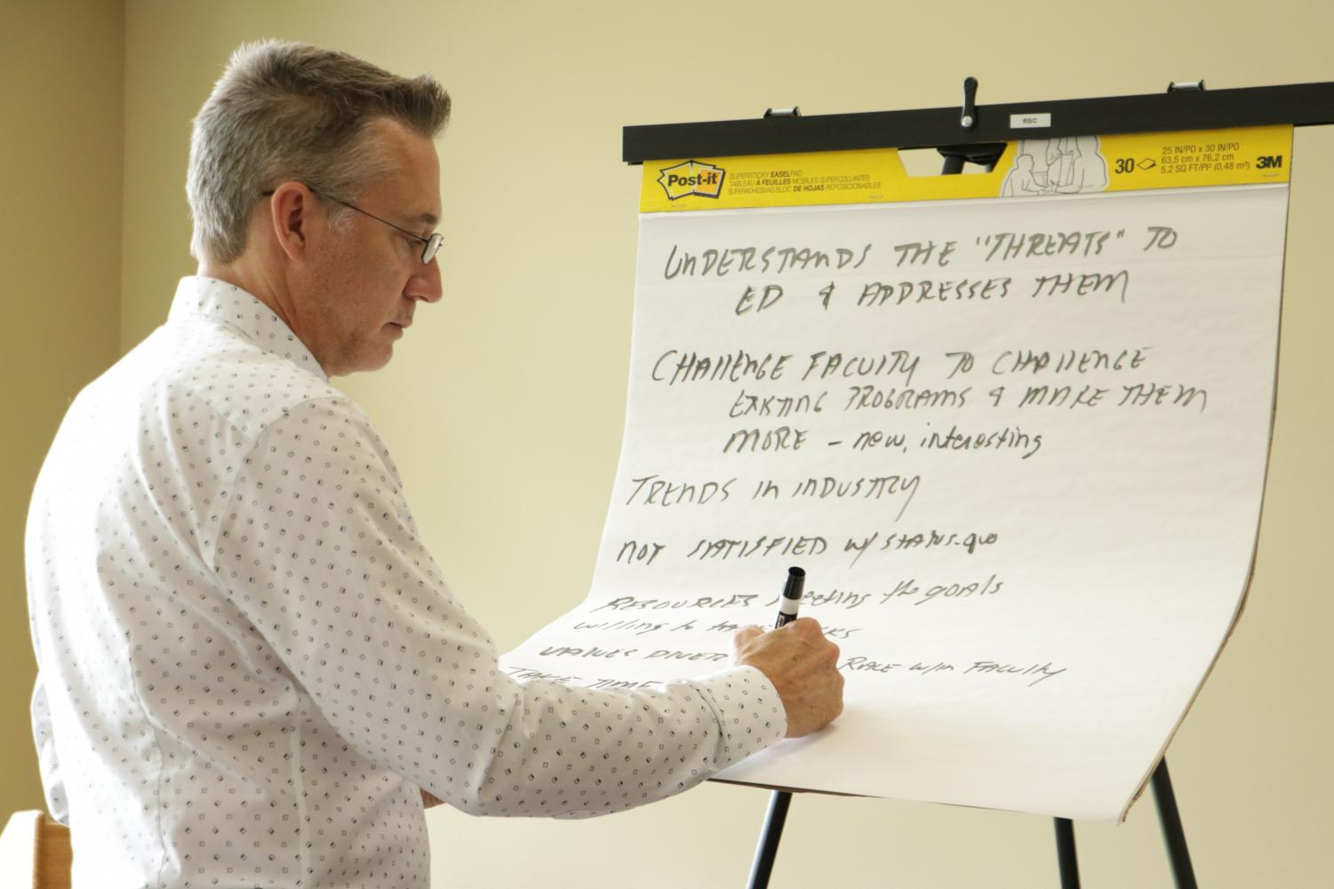 Michael Ballew, a senior partner with Wheless Partners, writes down feedback during a public forum. Wichita State is paying the firm to help find candidates for its presidency.